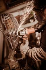 Metal worker Grinding with sparks in workshop