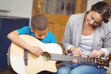 Pretty teacher giving guitar lessons to pupil