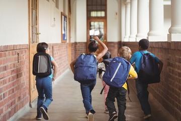 Rear view of happy pupils walking at corridor