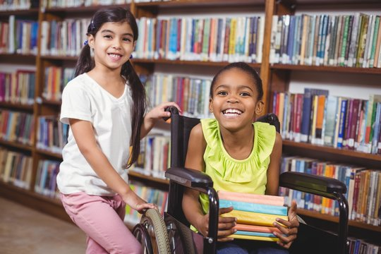 Smiling pupil in wheelchair holding books in the library
