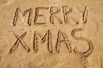 The words Merry Xmas written in the sand on the beach