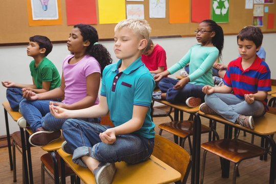 Pupils meditating on classroom desks