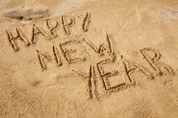 The words Happy New Year written in the sand on the beach