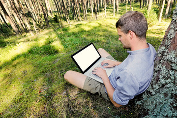 man is sitting against a tree in the forest, working with his la