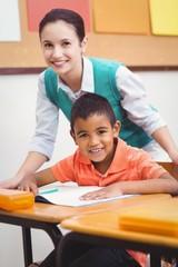 Teacher helping a little boy during class