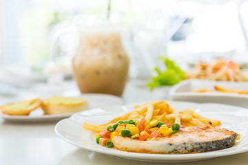 Grilled salmon steak meal served with salad and French fries