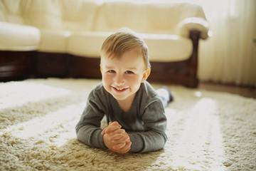 little boy lying on the carpet