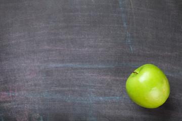 Green apple on blackboard or chalkboard background