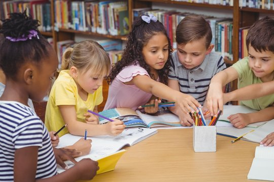 Pupils working together at desk in library