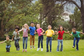 Fototapeta Cute pupils cheering on the grass outside  obraz