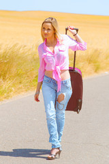 hitchhiking woman walking with her suitcase down the road