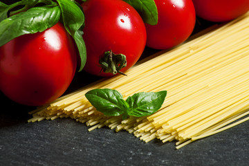 Concept of italian food with pasta, tomato and basil, selective