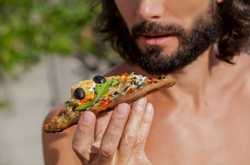 hungry man biting, eating slice of pizza  portrait of a young man eating pizza against a nature background