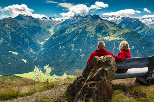 senior couple sitting in austrian alps and watching peaks with glacier and clouds