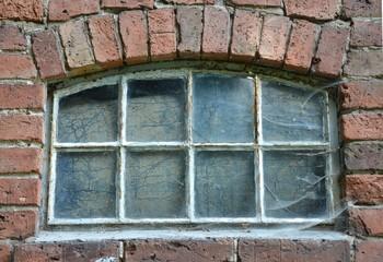 Sehr altes Rundbogenfenster mit Spinneweben