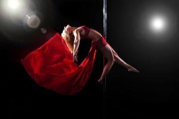 Junge Sportlerin macht Poledance Posen mit rotem Tuch