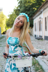 Romantic girl with bicycle and flowers