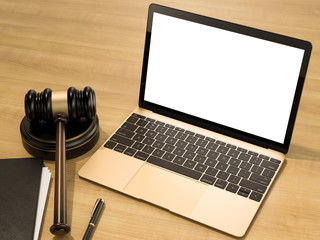 Wooden judges gavel and laptop on the wooden background