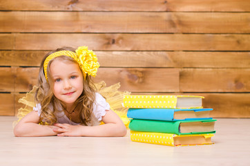 little girl with wreath lying near stack of books