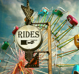 aged and worn vintage photo of rides sign with ferris wheel at carnival