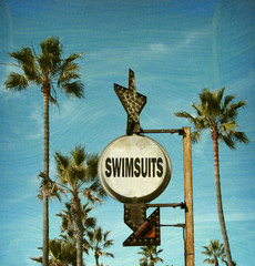aged and worn vintage photo of swimsuit beach sign
