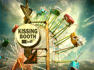 aged and worn vintage photo of kissing booth sign at carnival with ferris wheel in background