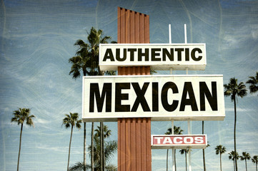 aged and worn vintage photo of mexican food sign with palm trees