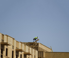 Construction on new building, man working on roof top