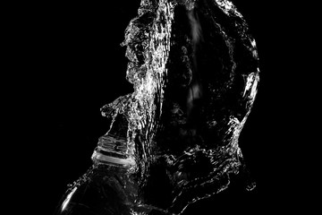 stream of water on black background departs from plastic bottle