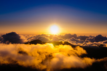 Sunrise over clouds and distant mountains from Haleakala Crater.
