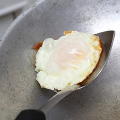 cooking fried egg in hot pan with oil