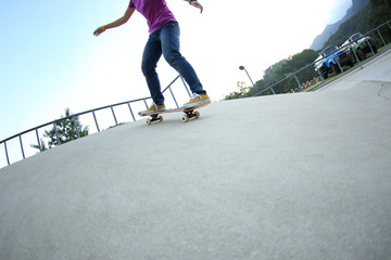 young woman skateboarder skateboarding at skatepark ramp