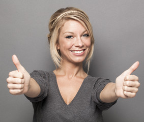 satisfaction concept - thrilled young woman with trendy blonde hair giving a double thumbs up for agreement
