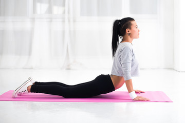 Girl doing warming up exercise for spine, backbend, arching