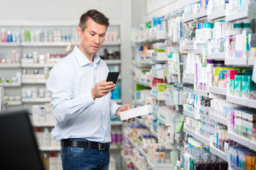 Consumer Checking Information On Mobile Phone In Pharmacy