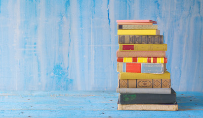 stack of books on grungy background, panoramic format, free copy