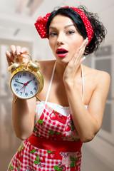 Pinup sensual girl in apron holding alarm clock