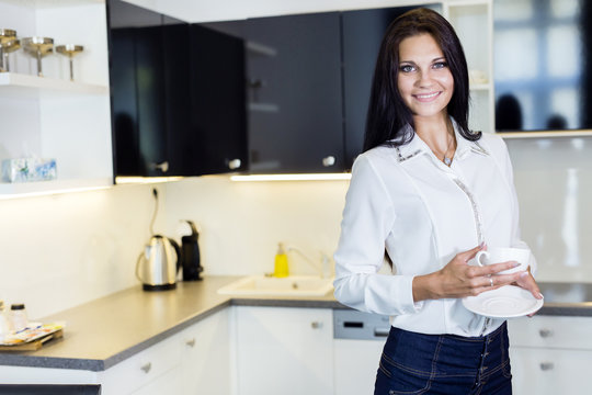 Beautiful woman holding a cup in a kitchen