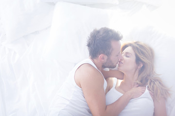 Romantic lovers kissing in bed