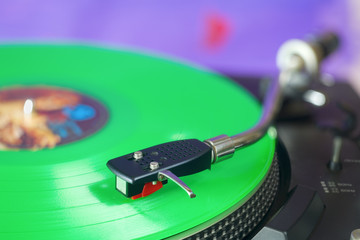 Retro turntable with green vinyl record, free copy space