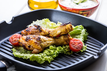 Grilling. Grilled chicken. Grilled chicken legs. Grilled chicken legs, lettuce and cherry tomatoes. Traditional cuisine. Mediterranean cuisine.