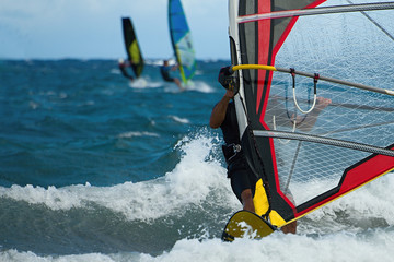 Three windsurfers in action