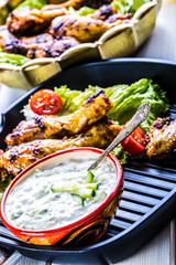Tzatziki sauce. Tzatziki dressing. Tzatziki dressing with grilled chicken legs and fresh vegetable,lettuce leaf and cherry tomatoes. Grilled chicken legs, lettuce and tomatoes. Mediterranean cuisine.