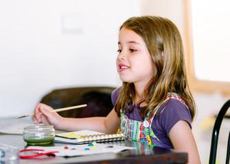 Portrait of a cute smiling girl painting a picture
