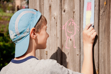 child drawing a chalk picture
