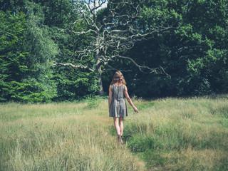 Young woman walking in meadow