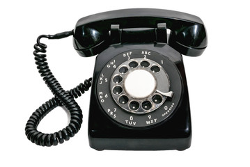 Old black vintage rotary dial telephone on white background