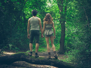 Young couple standing on a log in the forest