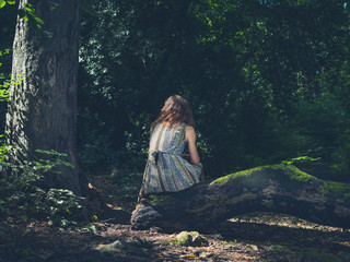 Woman sitting on log in forest