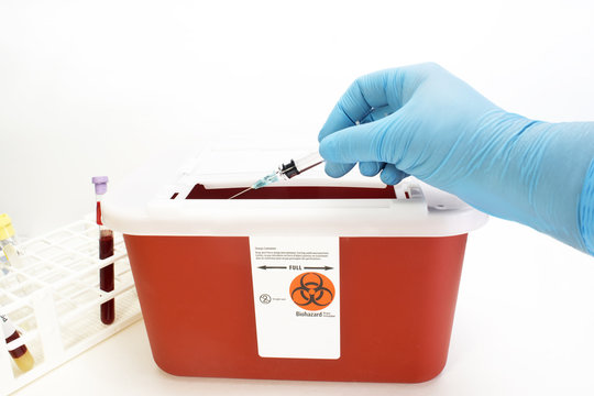 Technician drops syringe into sharps container.
